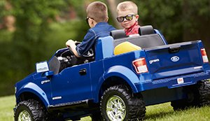 Boys driving Power Wheels jeep